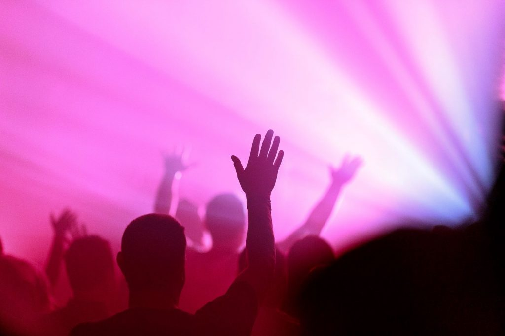 picture of pink rays of light and hands raised in praise   James Coleman on Unsplash