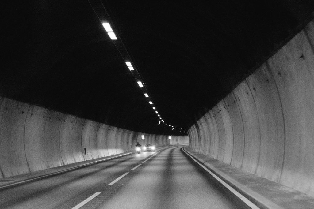 """black and white tunnel with little traffic in Norway illustrating loneliness, questioning and darkeness of asking """"How long?"""""""
